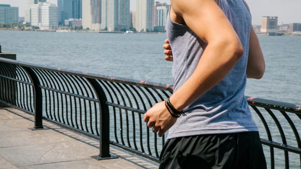 мужчина бежит по набережной с фитнес-браслетом на руке
