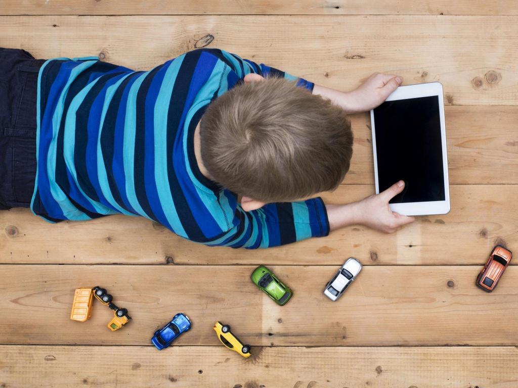 мальчик с планшетом возле игрушечных машинок